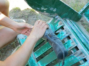 Krista uses an electrical sander to smooth out the surface of the wood and paint still left on the chair.