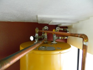 Cold enters from the back wall to the right. Hot water from the stove enters the center of the tank where the old T & P valve was. Howater leaves the tank from the pip on the left with the pressure gauge and new t&P valve and enters the back wall and travels throughout the home to each faucet. Note extra valves placed to eventually plump for a solar hot water system to be placed on the roof for summer heating.