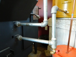 Cold water leaves the tanks original emergency drain valve and enters the wood stove's fire box in the lower pipe. Hot water exits the wood stove through the upper pip and enters the hot water storage tank. The water circulates in the motion building heat until hot water is stored and ready for use.