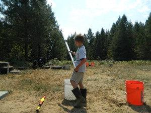 Ready, aim, douse... Our son tests the homemade water gun preparing for a battle with a friend on a hot sunny day.
