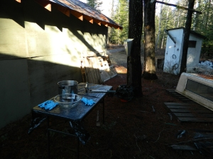 Making preparations... Here is out setup behind our wood shed. We attached the killing cone to a tree and the had a bucket placed below. We also set up the table, with clean warm water, towels, sharpened knives, and protected the top with clean garbage bags.