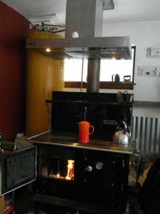 Fired up... The water tank that holds the hot water from the stove is a converted electric water heater (Yellow) to the left. The copper pipe seen next to the stove pipe is the emergency pressure relief system. The orange french press on the stove is my morning coffee.