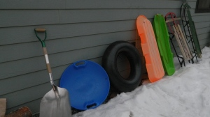 The line up...Starting from left to Right our snow shovel, disc, tibe, plastic sled tobaggon orange and green, the Topedo sled, and the green sled we call the General.